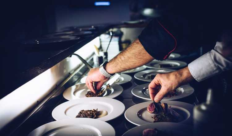 two chefs adding final touches to plating food