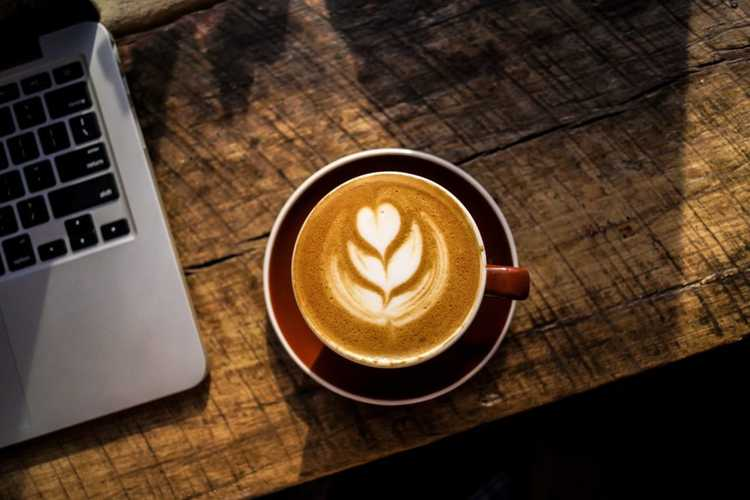 laptop and cup of cappuccino on wooden table