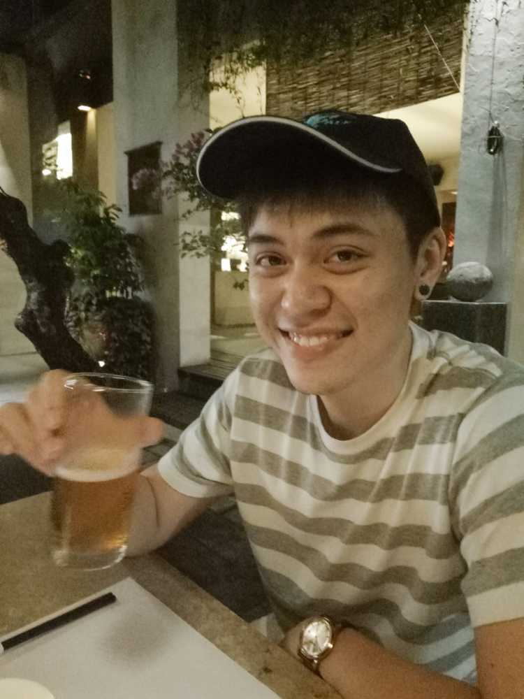 nick ang first photo with earring and beer in hand in bali restaurant