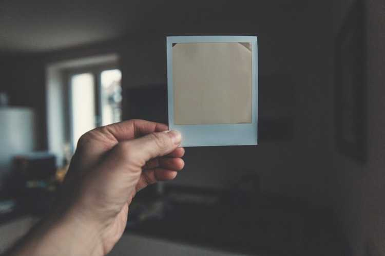 hand holding a white washed polaroid