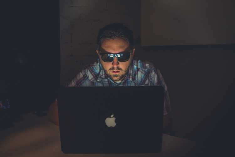 guy wearing shades working on laptop in a dark room